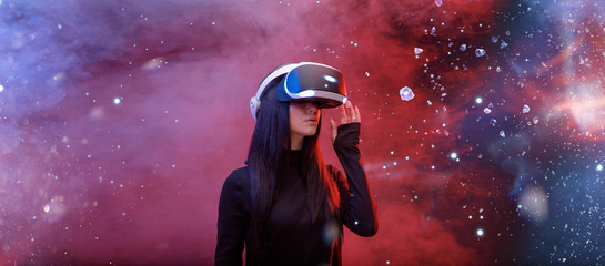 Wall Mural - Beautiful woman with flowing hair in futuristic dress over dark space magic background. Girl in glasses of virtual reality. Augmented reality, game, future technology concept. VR.