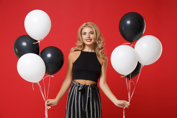 Smiling young woman girl in black clothes posing isolated on red background studio portrait. St. Valentine's Day, birthday holiday party concept. Mock up copy space. Celebrating, holding air balloons.