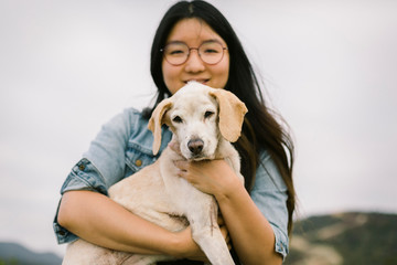Portrait of smiling woman holding puppy
