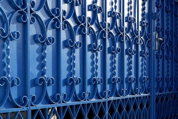 Sunlight and shadow on surface of wrought-iron elements pattern of vintage blue metal gate door decoration, exterior architecture concept