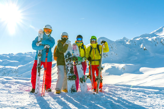 Four happy friends snowboarders and skiers are having fun on ski slope with ski and snowboards in sunny day.
