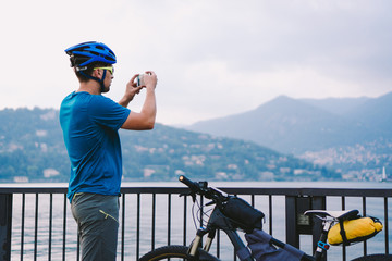 Cyclist taking pictures with smart phone. Caucasian man in bike helmet taking photo of landscape. Outdoor activity. Tourist makes photo of Lake Como in Italy