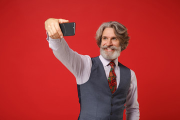 Smiling elderly gray-haired mustache bearded man in classic shirt vest colorful tie posing isolated on red background. People lifestyle concept. Mock up copy space. Doing selfie shot on mobile phone.