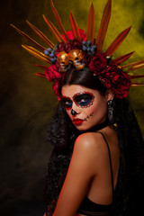Creative image of Halloween makeup look or Dia De Los Muertos holiday on dark background with copyspace. Beautiful Model wearing a headpiece with red roses