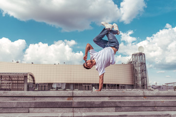 dancer on one arm dances break dance, hip-hop, artist acrobat. Summer city, clouds background. Active youth lifestyle, young male dancer, fitness movement workout breakdancer. Free space for text.