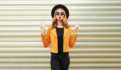 Cool girl blowing red lips sending sweet air kiss wearing yellow jacket, black round hat on wall background