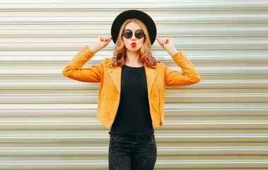 Beautiful woman model blowing red lips sending sweet air kiss wearing yellow jacket, black round hat on wall background
