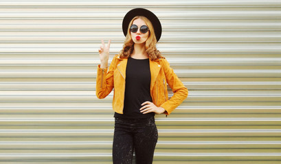 Young woman blowing red lips sending sweet air kiss wearing yellow jacket, black round hat on wall background