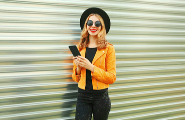 Stylish smiling woman with phone wearing yellow jacket, black round hat on metal wall background