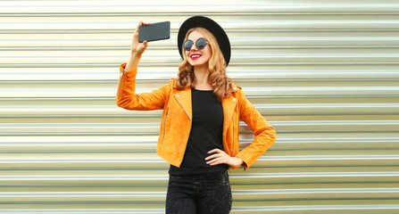 Stylish happy smiling woman taking selfie picture by smartphone wearing yellow jacket, black round hat on metal wall background