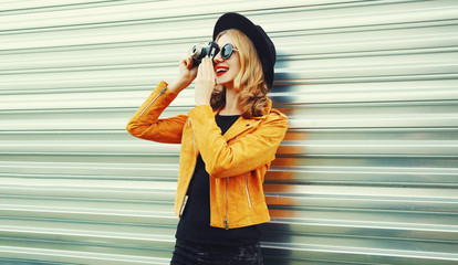 Stylish smiling woman with retro camera taking picture wearing yellow jacket, black round hat on metal wall background