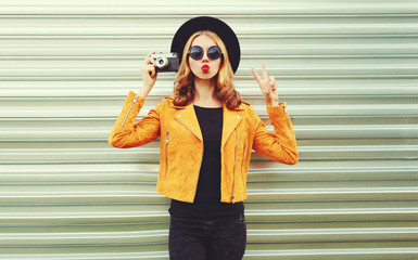 Stylish woman with retro camera taking picture wearing yellow jacket, black round hat on metal wall background