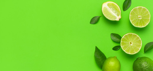 Wall Mural - Fresh juicy lime and green leaves on bright green background. Top view flat lay copy space. Creative food background, tropical fruit, vitamin C, citrus. Composition with whole and slices of lime