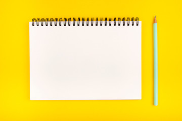 Empty notebook and pencil on yellow background, top view. Copy space.
