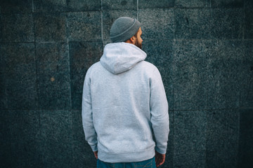 City portrait of handsome hipster guy with beard wearing gray blank hoodie or hoody and hat with...
