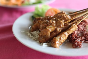 Wall Murals Ready meals Closeup shot of delicious chicken satay with rice in a white plate