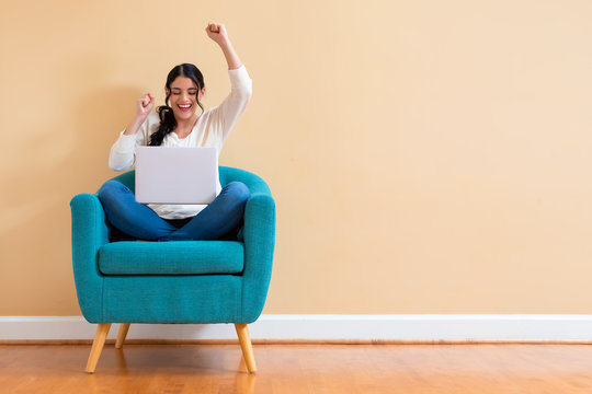 Young woman with a laptop computer with successful pose sitting in a chair