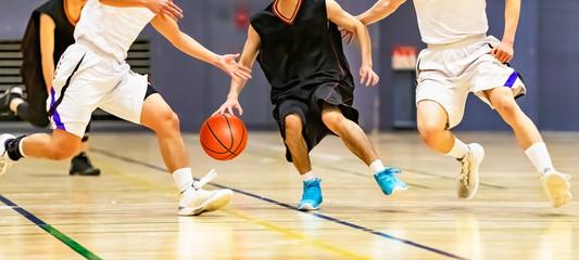 バスケットボールの試合をする大学生