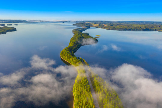 Aerial view of Pulkkilanharju Ridge, Paijanne National Park, southern part of Lake Paijanne. Landscape with drone. Fog, Blue lakes, fields and green forests from above on a sunny summer morning.