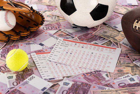 baseball glove and ball, soccer, tennis and rugby balls near betting lists on euro and dollar banknotes, sports betting concept