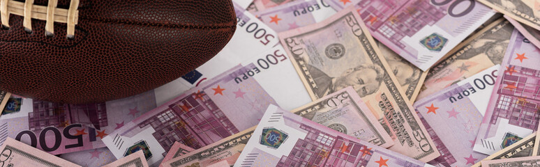 panoramic shot of rugby ball on euro and dollar banknotes, sports betting concept