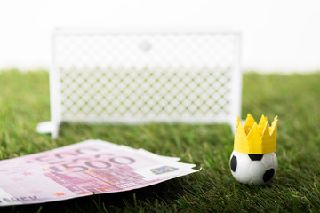 selective focus of toy soccer ball with paper crown near euro banknotes and miniature gates isolated on white, sports betting concept