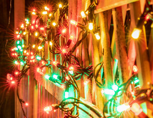 Very shiny Christmas decorations outside at night in Northern countries, Led lamps usage to save energy for green environment, blurred close up photo - lamps hung on wooden fence. Sweden