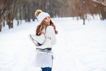 Poster Glisse hiver Beautiful woman weared in white sweater and hat with ice skates on the back walks in winter snowy park.
