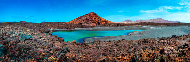 Impressive and scenic volcanic nature unique in Timanfaya National Park.Red mountain and green puddle near the sea coast in Canary island,Lanzarote.Spain beachs
