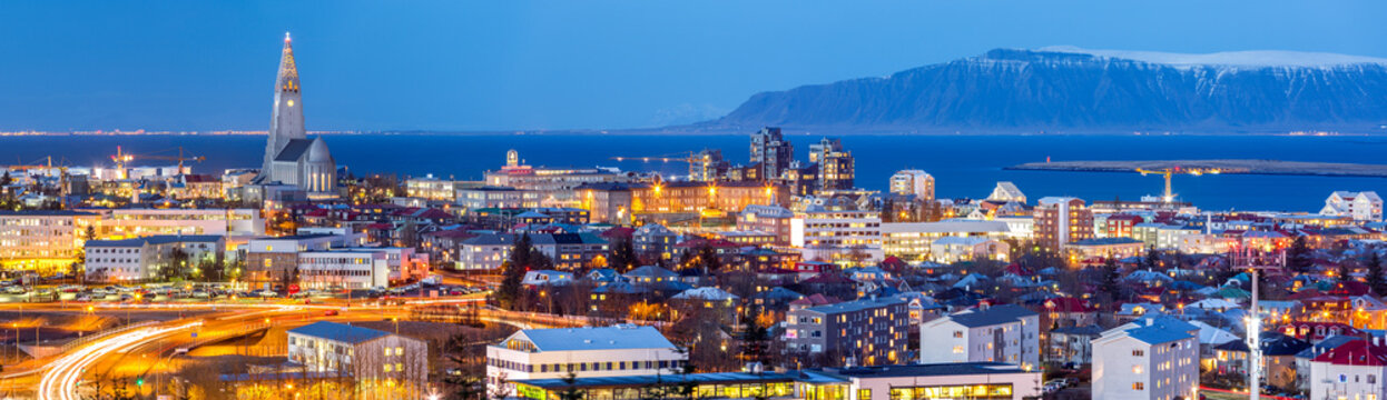 Aerial view of Reykjavik at dusk. Hallgrimskirkja church dominates the skyline and snow capped mount Esja the background