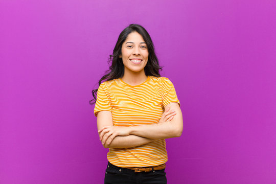 young pretty latin woman looking like a happy, proud and satisfied achiever smiling with arms crossed against purple wall
