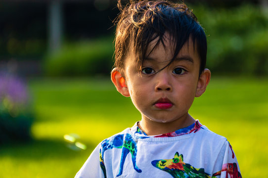 Cute Mexican American boy child is playing in a park in the city. Looking at camera.