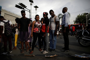 People look at pictures of victims of previous clashes during a gathering of protesters to demand the resignation of Haitian President Jovenel Moise, in the streets of Port-au-Prince
