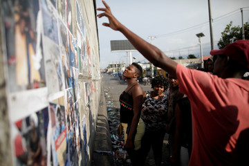People look at pictures of victims of previous clashes during a gathering of protesters to demand the resignation of Haitian President Jovenel Moise, in the streets of Port-au-Prince, Haiti