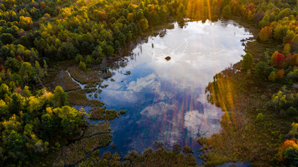 aerial perspective.  sunset on pond with sun streaks cascading in photo reflections on pond with beaver hut