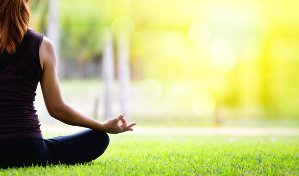 shots of young woman practicing yoga in nature. Sit on green grass at golden light at sunset . Communicate to exercise and maintain good health . Green color of the grass makes you feel fresh.