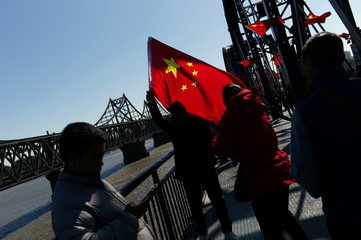 Chinese visitor poses for picture with a Chinese flag on the Broken Bridge near the Friendship Bridge which connects North Korea's Sinuiju and China over the Yalu river, in Dandong