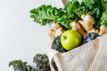 Cotton eco bag with vegetables on a light background, copy space. Ingredients for healthy food. Close up.