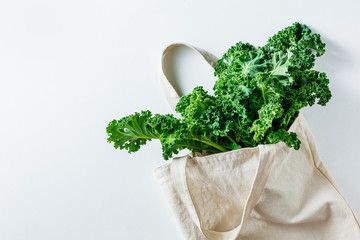 Fresh Kale leaves in a canvas bag. Eco friendly shopping. Healthy product. Top view, copy space.