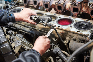 diesel truck engine repair service. Automobile mechanic tightening using wrench