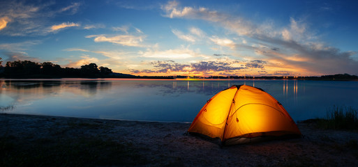 Photo sur Aluminium Camping Orange tourist lit tent by the lake at sunset