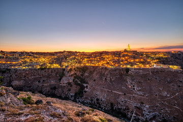View of the beautiful old town of Matera and the canyon of the Gravina river after sunset
