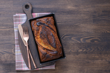 Homemade banana bread with cinnamon on a wooden background, close up, top view