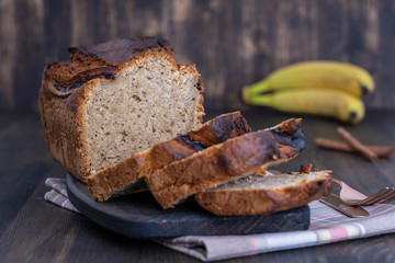 Homemade banana bread with cinnamon on a wooden background, close up