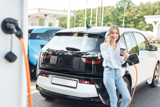 Young adult woman standing on parking, charging electric car, talking on smartphone
