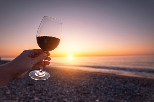 Person holding glass of red wine during watching sunset and enjoying sea holiday