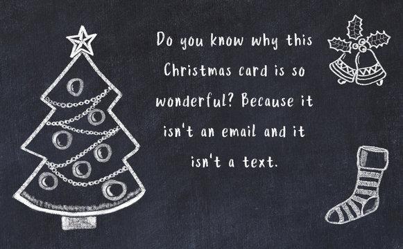 Drawing of christmas tree and handwritten greetings on black chalkboard