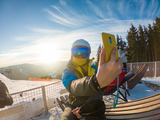 woman in ski equipment taking selfie on sunset in snowed mountains