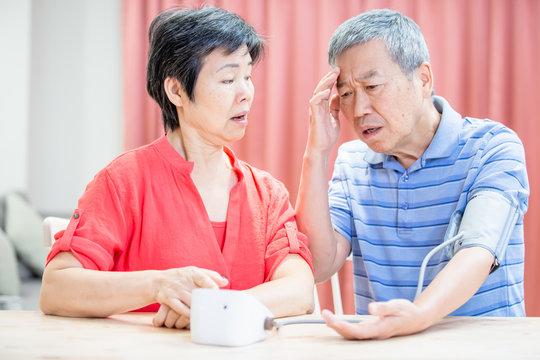 elder couple use blood manometer
