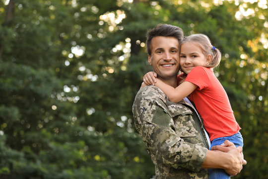 Father in military uniform holding his little daughter at green park